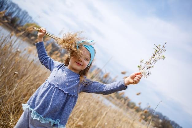 Kleines mädchen hält trockenes schilf und einen zweig mit kleinen weißen blüten in den händen, sonniges frühlingswetter, lächeln und freude am kind