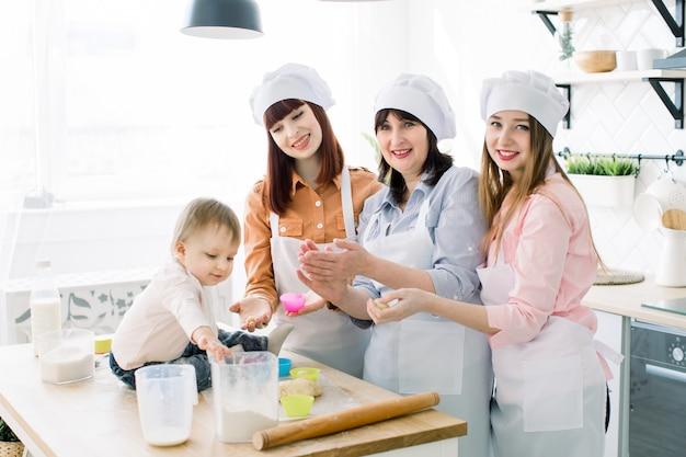 Kleines mädchen hilft, zusammen mit mutter, tante und großmutter cupcakes zu machen. hübsche frauen lächeln und haben spaß beim gemeinsamen backen in der küche zu hause