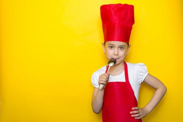 Kleines mädchen im anzug eines roten chefs lecken den löffel, köstlichen geschmack
