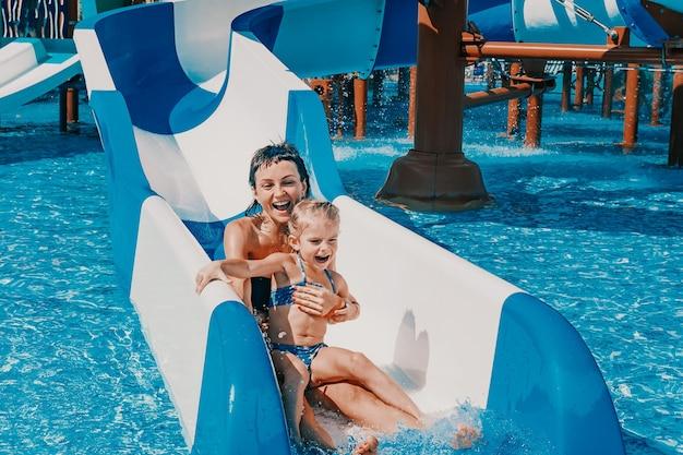 Kleines mädchen im badeanzug geht die blauen rutschen hinunter zum pool mutter und tochter spielen und schwimmen im außenpool