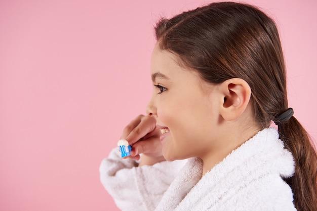 Kleines mädchen im bademantel putzt zähne