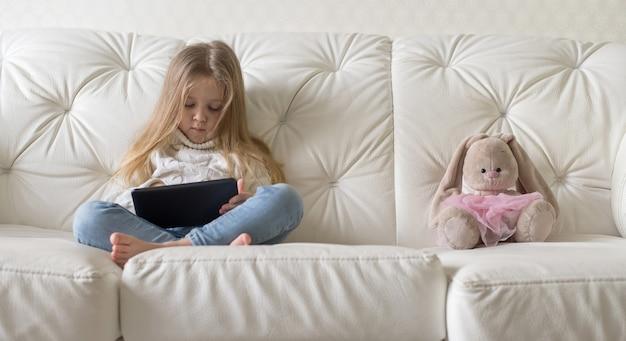 Kleines mädchen im bett, das eine tablette im sozialen internet spielt.