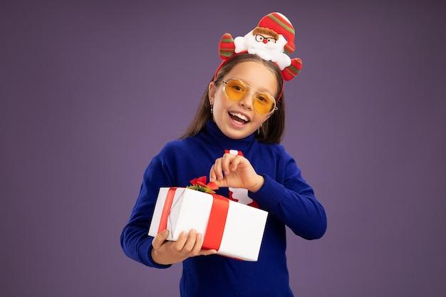 Kleines mädchen im blauen rollkragenpullover mit roter krawatte und lustigem weihnachtsrand auf dem kopf, der ein geschenk mit einem lächeln im gesicht hält, das glücklich und fröhlich über der lila wand steht