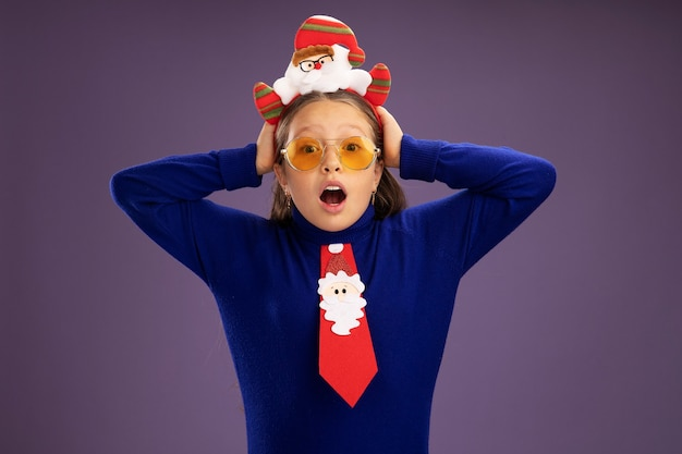 Kleines mädchen im blauen rollkragenpullover mit roter krawatte und lustigem weihnachtsrand auf kopf besorgt und überrascht mit händen auf ihrem kopf