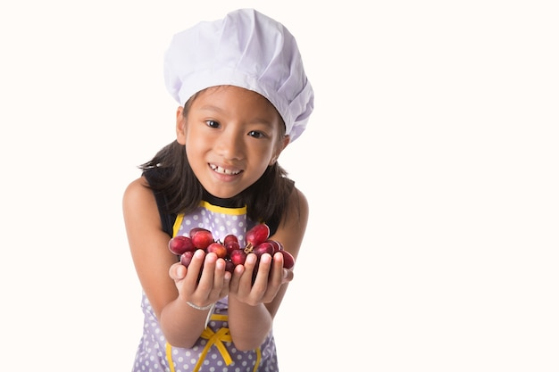 Kleines mädchen im chefkleid, das in der hand traube oder frucht lokalisiert auf weißem hintergrund hält