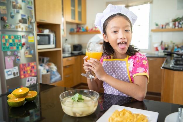 Kleines mädchen im chefkleid, das orangensaft in der küche trinkt