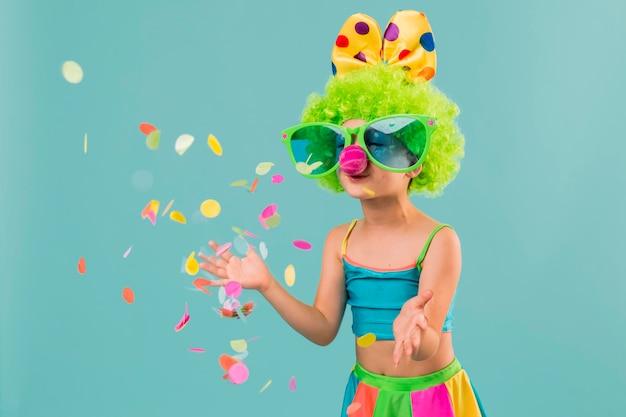 Kleines mädchen im clownkostüm mit konfetti