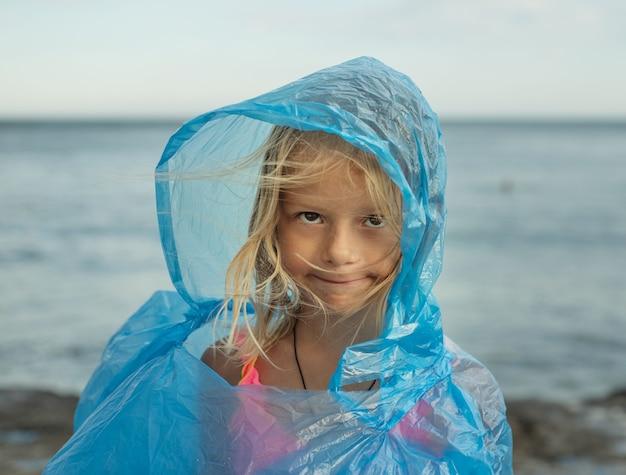 Kleines mädchen im durchsichtigen plastikregenmantel an einem windigen tag am strand, launischer tag am strand