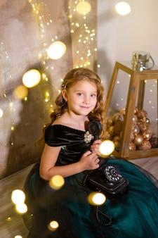 Kleines mädchen im festlichen kleid mit retro-telefon, weihnachtsschmuck, neujahrsfeiertage