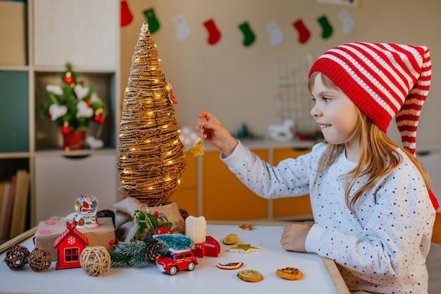 Kleines mädchen im gnomenhut verzierte weihnachtsbaum mit trockenen orangefarbenen stücken im kinderzimmer