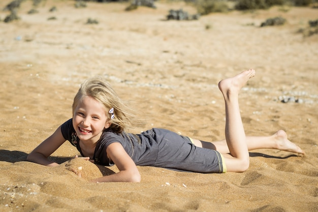 Kleines mädchen im grauen kleid steht auf dem heißen sand still.