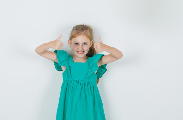 Kleines mädchen im grünen kleid, das daumen hoch zeigt und fröhlich aussieht