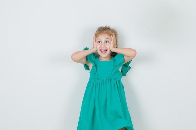 Kleines mädchen im grünen kleid, das kopf mit händen hält und glücklich schaut