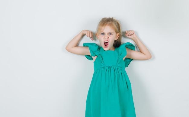 Kleines mädchen im grünen kleid, das muskeln wütend zeigt