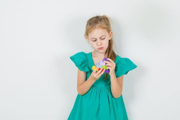 Kleines mädchen im grünen kleid, das stapel von spielzeugblöcken hält