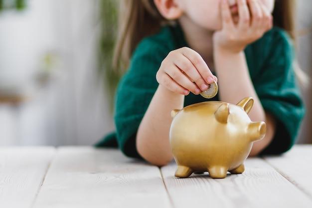 Kleines mädchen im grünen kleid, das über ihre geldausgabe nachdenkt und eine münze in ein sparschwein steckt