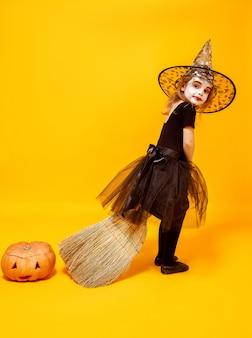 Kleines mädchen im halloween-hexenkostüm auf bräutigam mit dem kürbis beiseite lokalisiert