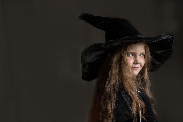 Kleines mädchen im halloween-hexenkostüm auf grauem hintergrund