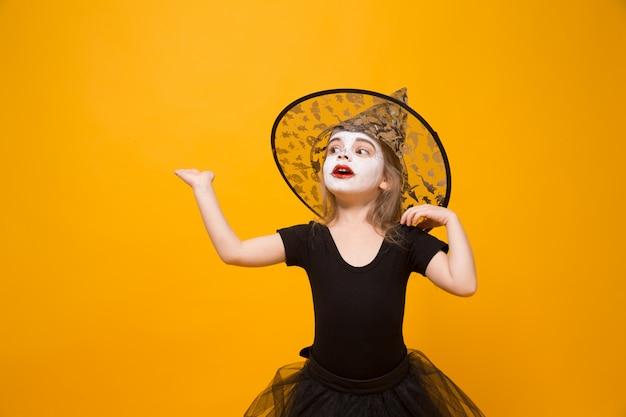 Kleines mädchen im halloween-hexenkostüm, orange oberfläche.