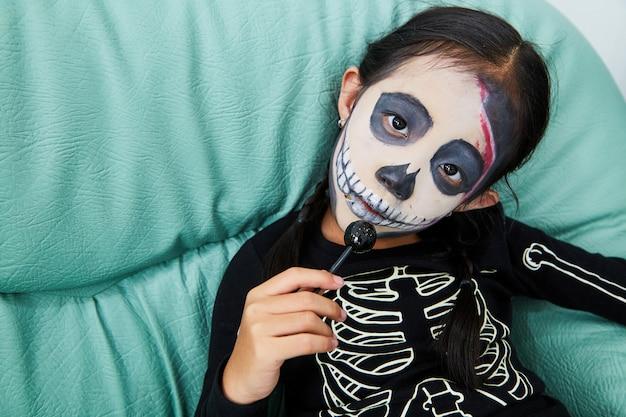 Kleines mädchen im halloween-kostüm zu hause