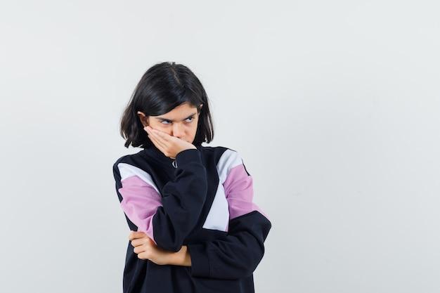 Kleines mädchen im hemd, das hand auf mund hält und traurige vorderansicht schaut.