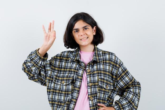 Kleines mädchen im hemd, jacke, die eine gute geste zeigt und froh aussieht, vorderansicht.