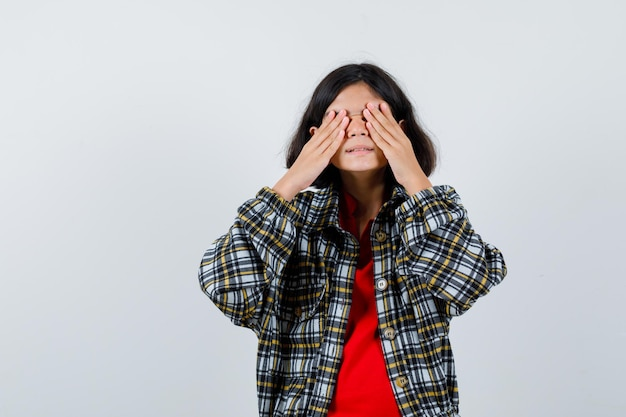 Kleines mädchen im hemd, jacke, die ihre augen mit den händen bedeckt und schüchtern aussieht, vorderansicht.
