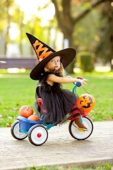 Kleines mädchen im hexenkostüm auf einem fahrrad mit kürbissen und süßigkeiten