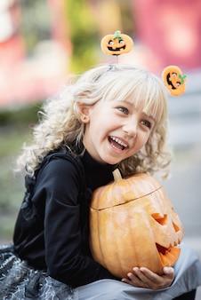 Kleines mädchen im hexenkostüm feiern halloween im freien und haben spaß.