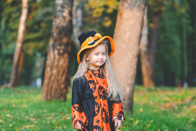 Kleines mädchen im hexenkostüm steht im herbst an halloween im park.