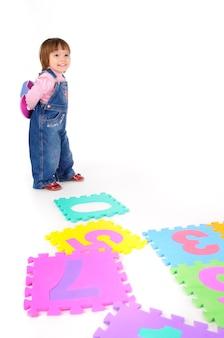 Kleines mädchen im jeansoverall, das zahlen lernt und zwei in der hand über weißem hintergrund im fotostudio hält