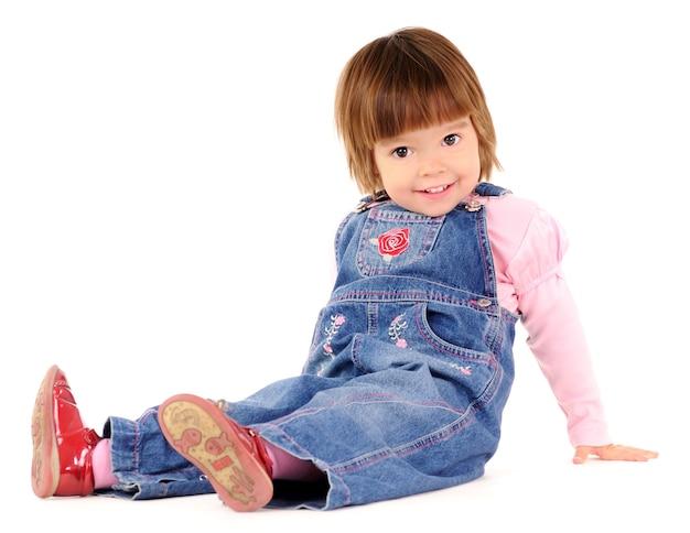 Kleines mädchen im jeansoverall, der auf boden sitzt und über weiße wand lächelt. schönes glückliches kinderlebensstilkonzept