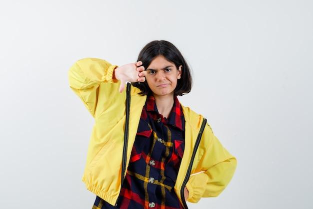 Kleines mädchen im karierten hemd, jacke, die daumen nach unten zeigt und selbstbewusst aussieht