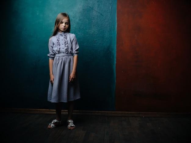 Kleines mädchen im kleid, das grünen studiohintergrund aufwirft. foto in hoher qualität