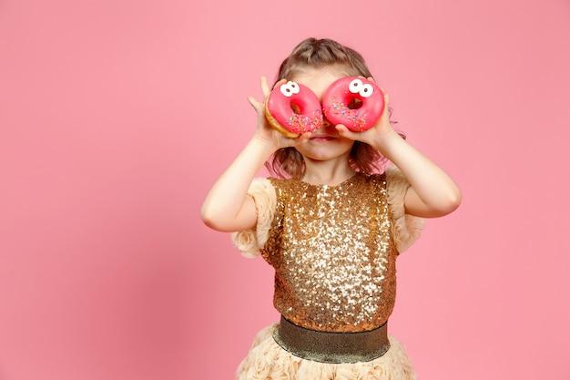 Kleines mädchen im kleid mit donuts