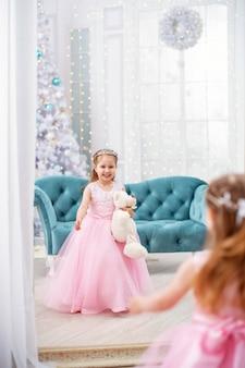 Kleines mädchen im kleid mit teddy mit sofa und weihnachtsbaum