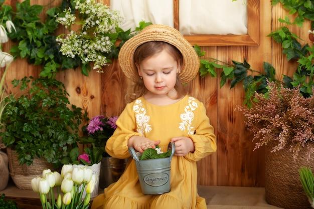 Kleines mädchen im kleid und im strohhut sitzt auf der veranda des holzhauses um grüne zimmerpflanzen und blumen. kind, das frühlingsblumen pflanzt. kind, das sich um pflanzen kümmert. kleiner gärtner pflanzt pflanzen im topf.