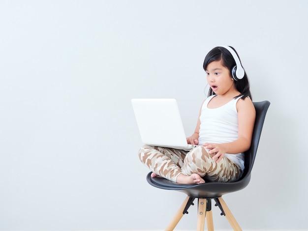 Kleines mädchen im kopfhörer mit laptop.