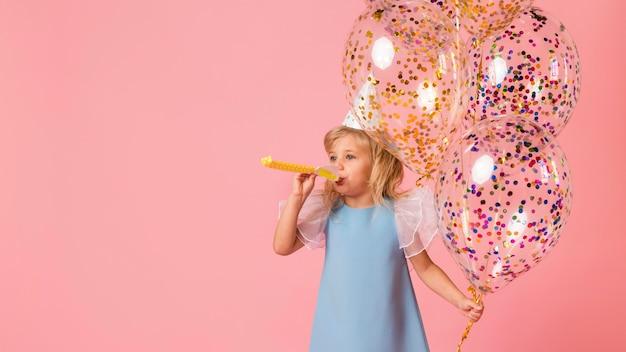 Kleines mädchen im kostüm mit luftballons