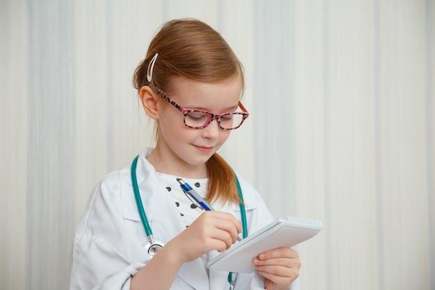 Kleines mädchen im mantel eines arztes lächelt und macht sich notizen in einem notizbuch.