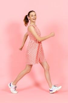 Kleines mädchen im niedlichen hellen kleid, das glücklich auf rosa aufwirft