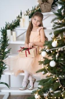 Kleines mädchen im prinzessinkleid feiert weihnachten