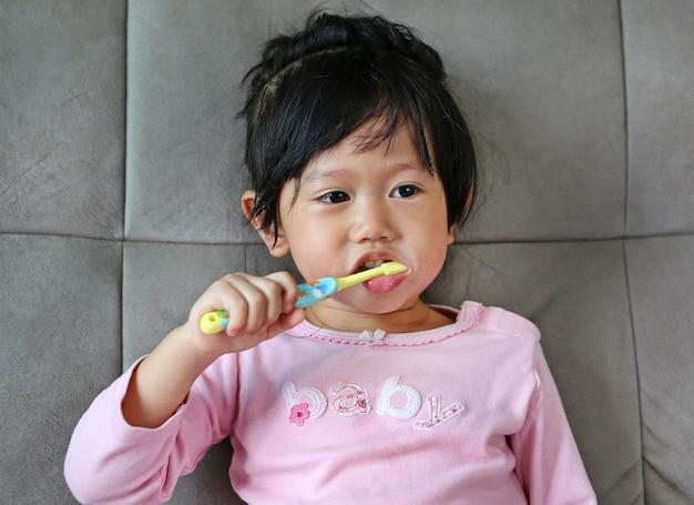 Kleines mädchen im rosa auf bürstenden zähnen des sofas