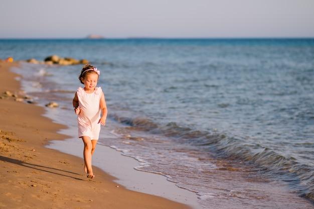 Kleines mädchen im rosa kleid, das auf dem strand bei sonnenuntergang läuft.