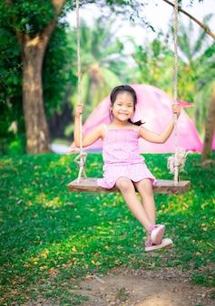 Kleines mädchen im rosa kleid, das auf einer schaukel beim zelten sitzt