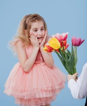 Kleines mädchen im rosa kleid erhält blumen, lokalisiert auf blauer wand, nahaufnahme, zwei kleine kinder.
