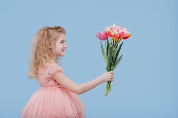 Kleines mädchen im rosa kleid mit frühlingsblumen in der hand, lokalisiert auf blauer wand, profilansicht
