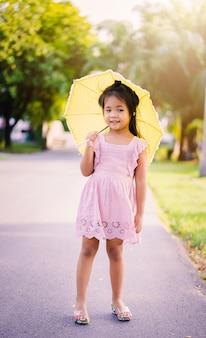 Kleines mädchen im rosa kleid mit gelbem regenschirm am sonnigen tag