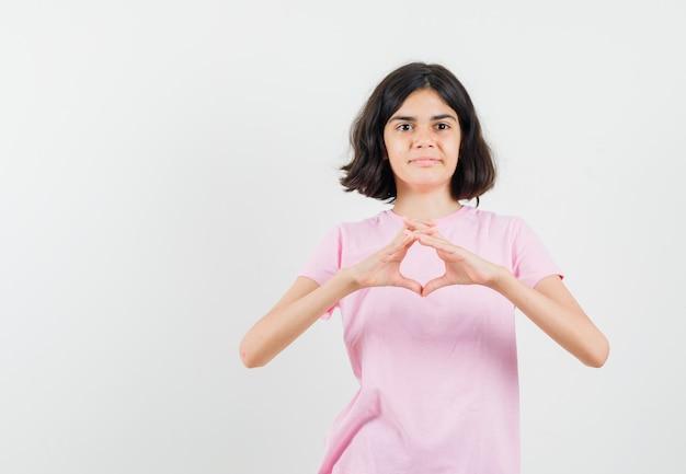 Kleines mädchen im rosa t-shirt, das herzgeste zeigt und fröhlich, vorderansicht schaut.