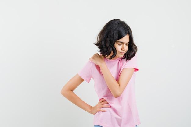 Kleines mädchen im rosa t-shirt, das schulterschmerzen hat und müde, vorderansicht schaut.